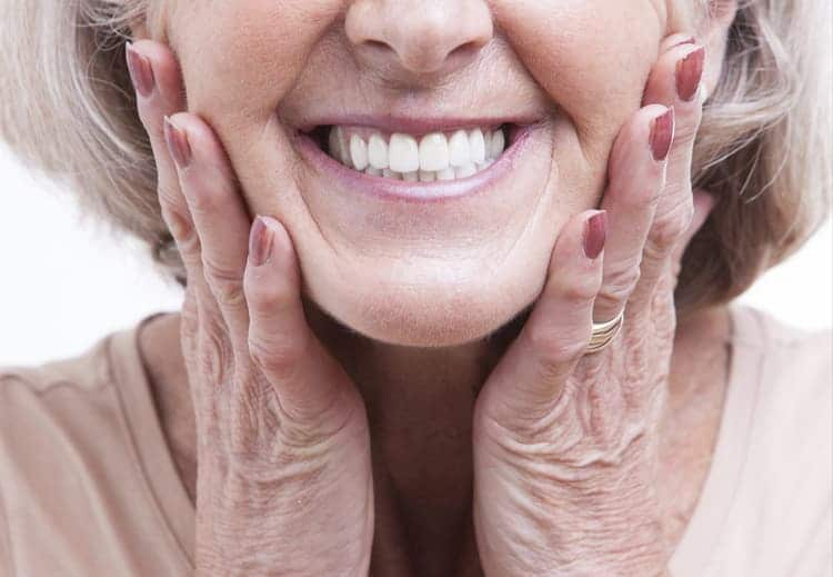 An older woman smiling as she touches her cheeks in excitement